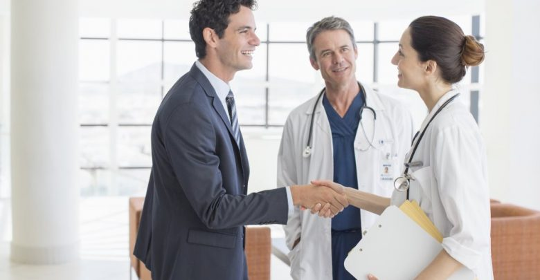 Doctors shake hands with businessman